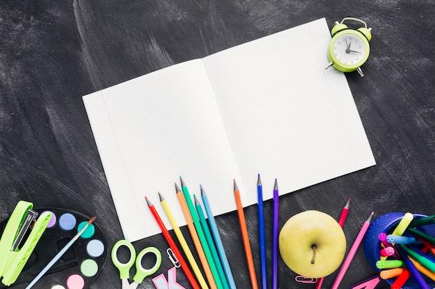 Nuevo cuaderno blanco junto a papelería brillante y manzana sobre fondo gris