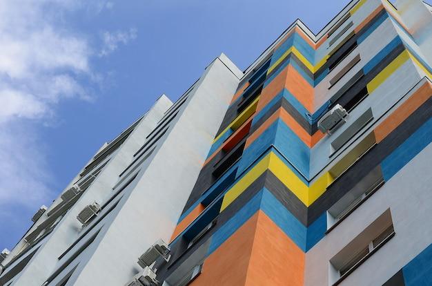 Nuevo edificio residencial de varias plantas y cielo azul.
