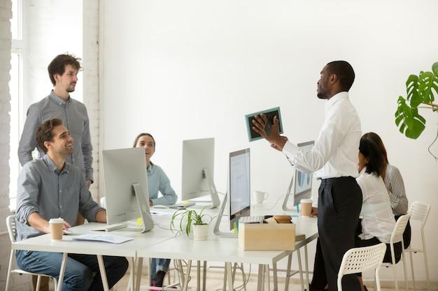 Nuevo empleado africano desempaquetado hablando en la primera oficina, día laborable