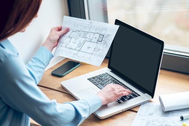 Nuevo enfoque. mujer involucrada atenta con dibujo en mano trabajando en la computadora portátil de pie cerca del alféizar de la ventana en el interior a la luz del día