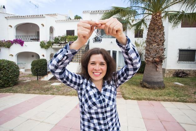 Nuevo hogar, casa, propiedad e inquilino - mujer joven divertida sosteniendo la llave frente a su nuevo hogar después de comprar bienes raíces.