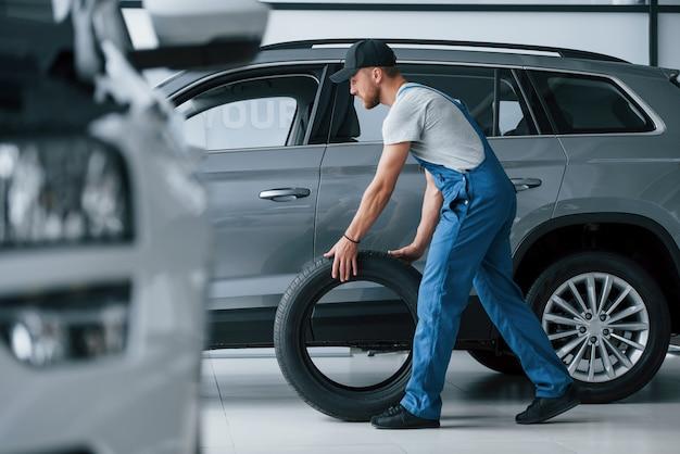 Uno nuevo. mecánico sosteniendo un neumático en el taller de reparación. reemplazo de neumáticos de invierno y verano