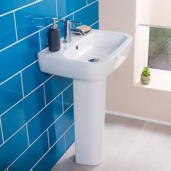 Nuevo y moderno grifo de acero con lavabo de cerámica en el baño.