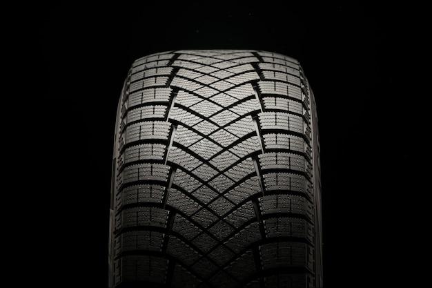 Nuevo neumático de invierno de fricción sobre un fondo negro, vista frontal de cerca.