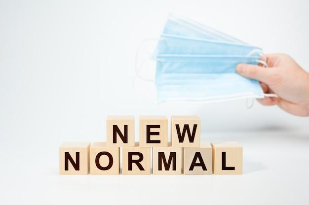 Nuevo texto normal en cubo de madera máscara protectora médica. cubos de madera con new normal
