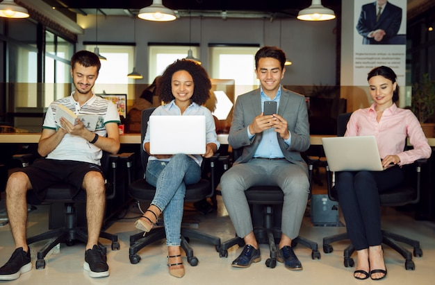 Nuevos candidatos con sus gadgets en la oficina.