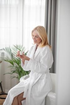 Nuevos cosméticos. una mujer rubia en una bata de baño blanca sosteniendo un tarro de una nueva crema