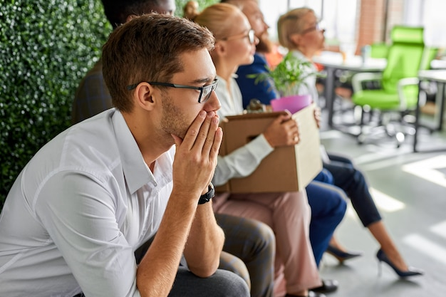 Nuevos empleados vinieron para una entrevista, un grupo de personas diversas en ropa formal se sientan en una línea preocupada