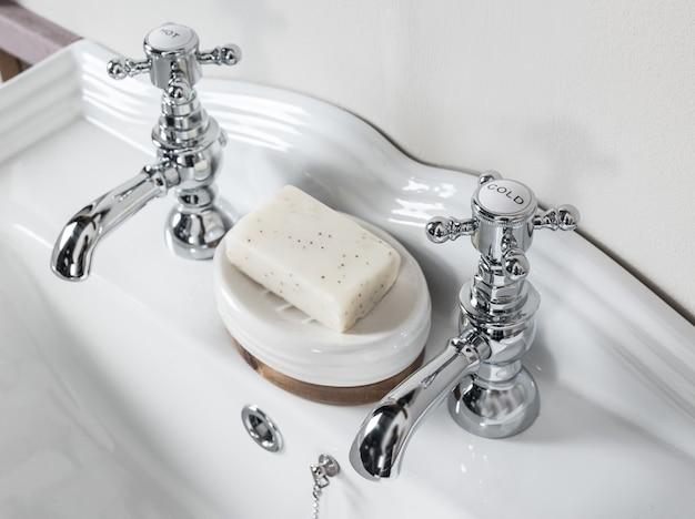 Nuevos y modernos grifos de acero con lavabo de cerámica en el baño.