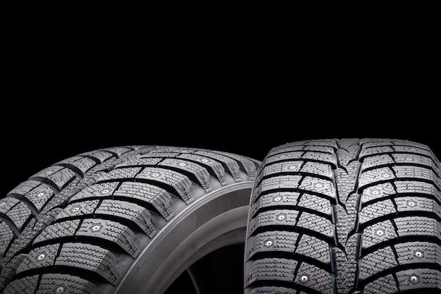 Nuevos neumáticos con tachuelas de invierno, aislados sobre fondo negro