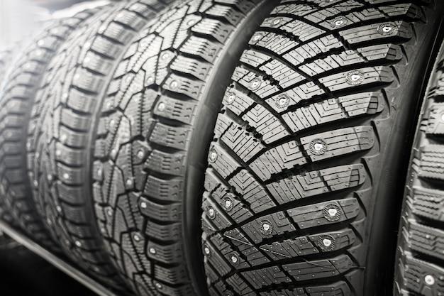 Nuevos neumáticos con tachuelas de invierno en la tienda. venta de ruedas de invierno. hielo, cambio estacional de neumáticos.
