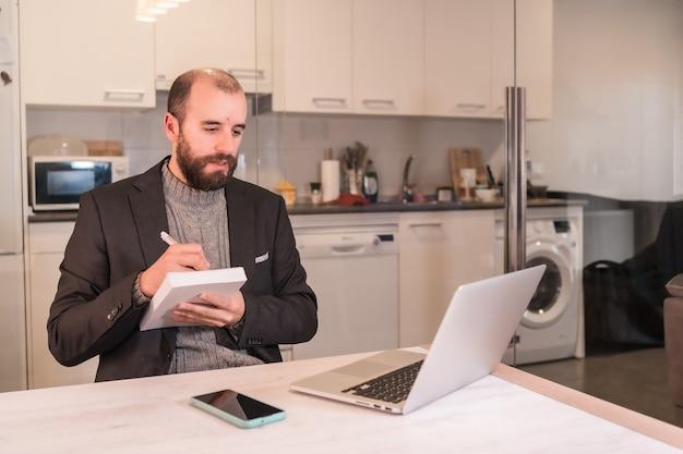 Nuevos normales durante la pandemia de coronavirus, niño empresario trabajando desde casa tomando notas en videollamada