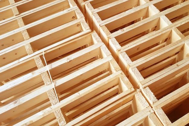 Nuevos palets de madera se apilan en el almacén de la empresa de entrega de carga.