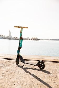 Nuevos scooters eléctricos estacionados cerca del muelle contra el mar idílico