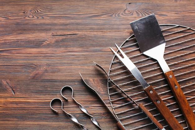 Nuevos utensilios metálicos de barbacoa sobre fondo de madera.