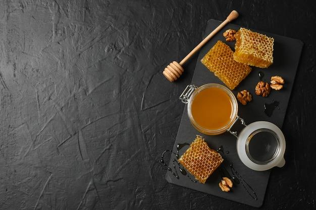 Nuez, panales, tarro con miel y cazo sobre fondo negro, espacio de copia