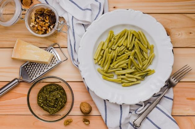 Nuez; queso; pasta y salsa de gemelli de espinaca en mesa de madera