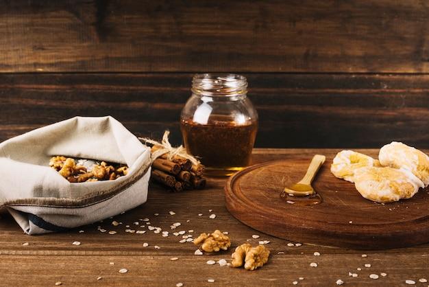 Nuez; rosquilla; miel y canela sobre superficie de madera.