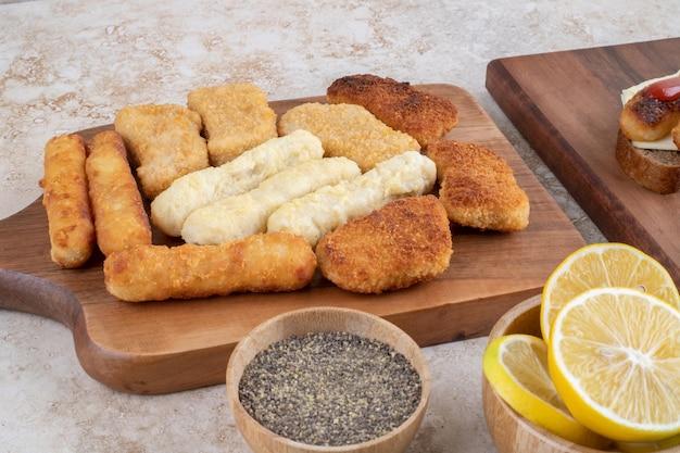 Nuggets crujientes, palitos de queso y salchichas a la parrilla en un plato de madera.