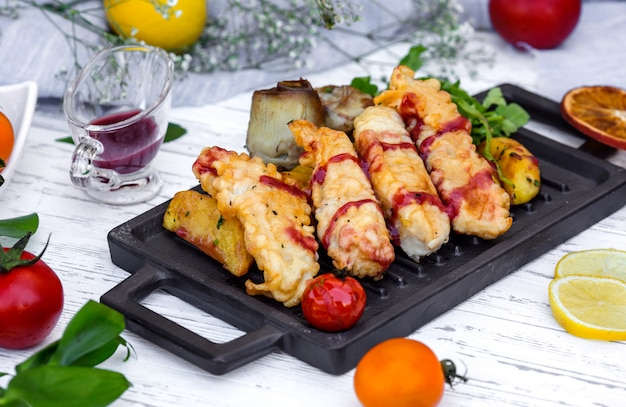 Nuggets de pescado crujientes servidos con potaot, salsa de granada y berenjena frita