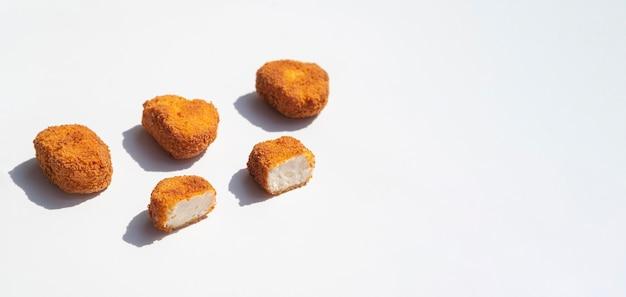 Nuggets de pollo alineados sobre fondo blanco.