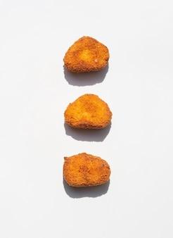 Nuggets de pollo alineados sobre fondo gris