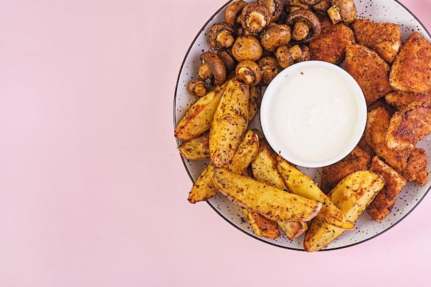 Nuggets de pollo de comida rápida con salsa de tomate, papas fritas, champiñones al horno y cola. vista superior