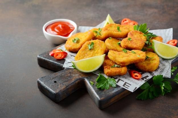 Nuggets de pollo frito crujiente con salsa de tomate en foco selectivo oscuro