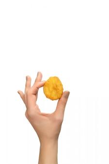 Nuggets de pollo frito en mano femenina sobre fondo blanco.
