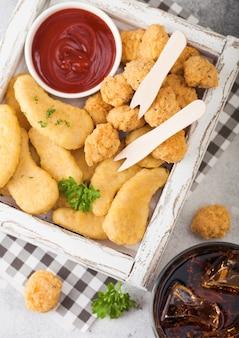 Nuggets de pollo con mantequilla y picaduras de palomitas de maíz en caja de madera vintage blanca con salsa de tomate y vaso de cola sobre fondo claro.