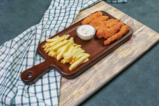Nuggets de pollo con papas fritas y un aderezo blanco.