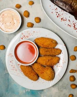 Nuggets de pollo picantes servidos con salsa de chile dulce