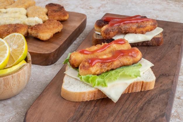 Nuggets de pollo y salchichas a la parrilla en tostadas de sándwich con hierbas y especias en un plato de madera.