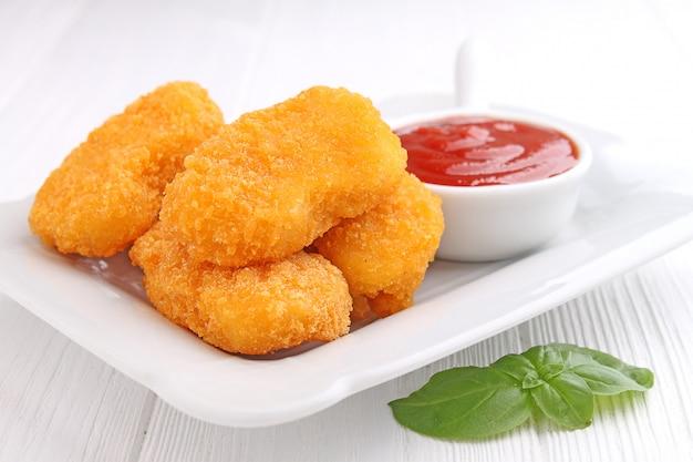 Nuggets de pollo con salsa de tomate decorados con albahaca en un plato blanco