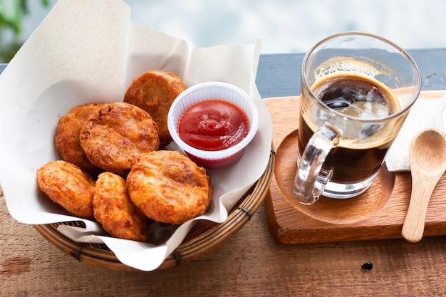 Nuggets de pollo con salsas y café recién hecho en un vaso