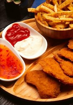 Nuggets de pollo servidos con papas fritas, salsa de tomate y mayonesa en una tabla de madera
