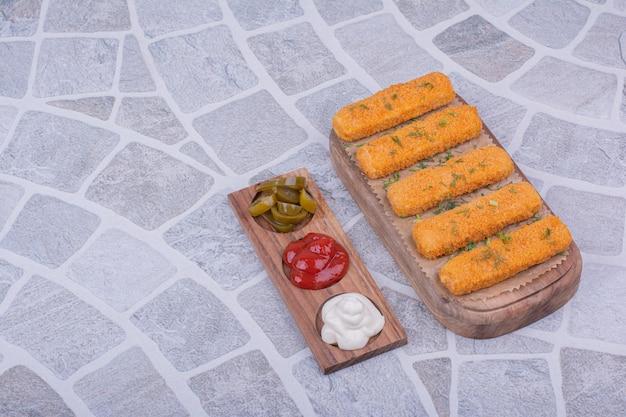 Nuggets de pollo con variedad de salsas en una tabla de madera
