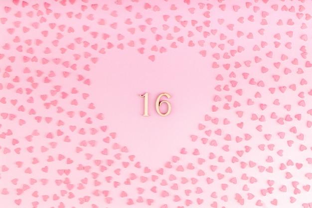 Número 16 dieciséis de madera en decoración en forma de corazón con corazones pequeños