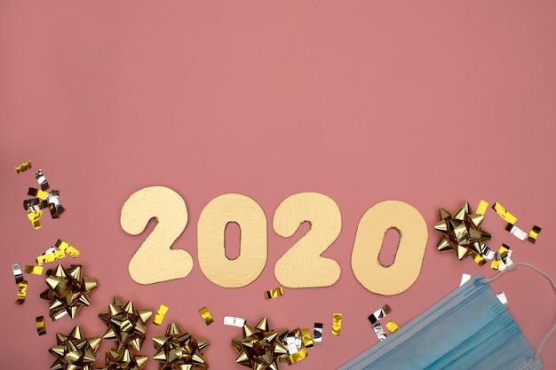 Número 2021 sobre fondo rosa decorado con confeti estrellado dorado