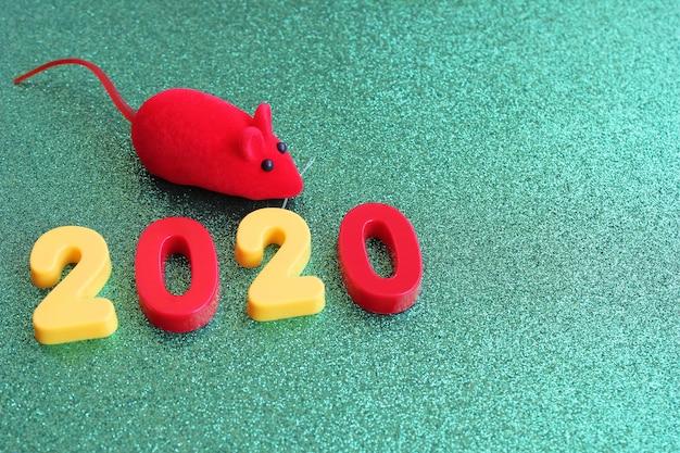 Número de año nuevo de 2020 y un ratón rojo de juguete en un verde