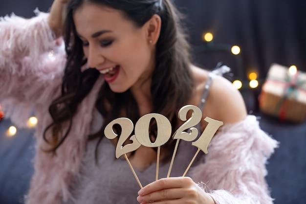 Número de año nuevo de madera en el fondo de una niña de cara feliz de cerca.