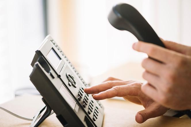 Número de marcación del hombre en el teléfono