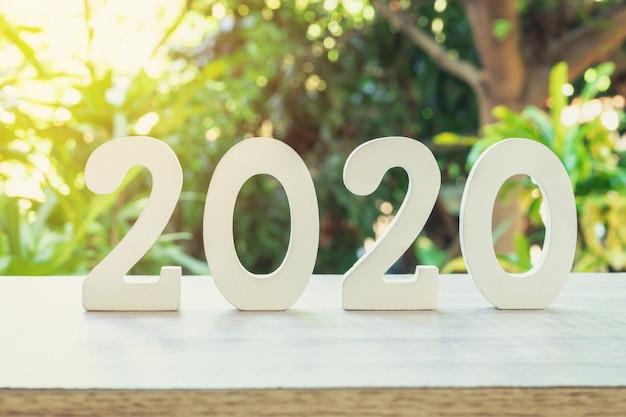 Número de madera 2020 para el nuevo año en la mesa de madera con luz solar.