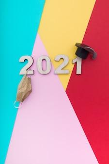 Número de madera 2021 en sombrero de graduación con máscara médica en superficie colorida