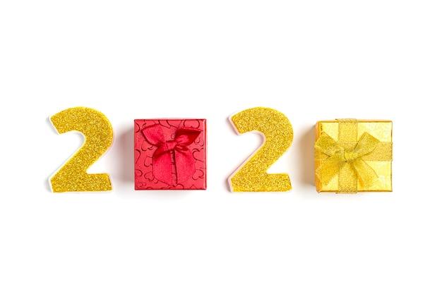 Números 2020 y caja de regalo roja, dorada decorada con destellos dorados aislados en blanco.