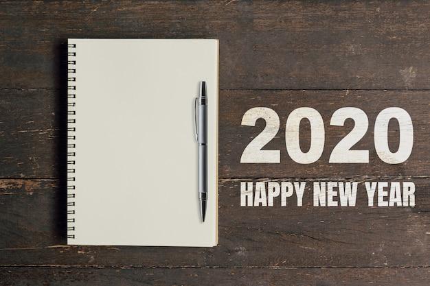 Números 2020 para feliz año nuevo y cuaderno en blanco con bolígrafo