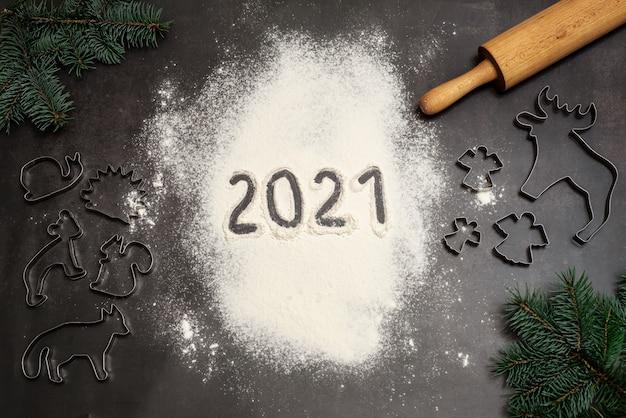 Números 2021 escritos a mano en harina con cortadores de galletas navideñas, rodillo y ramas de pino