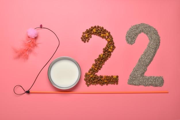 Los números 2022 se presentan con objetos para animales sobre un fondo rosa.