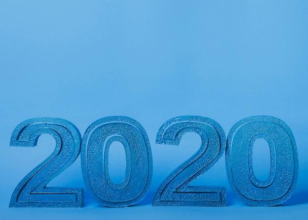Números de año nuevo 2020 sobre fondo azul con espacio de copia
