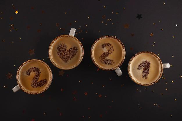 Números de año nuevo en tazas de café con espuma escritas a partir de cacao en polvo sobre fondo negro entre estrellas doradas